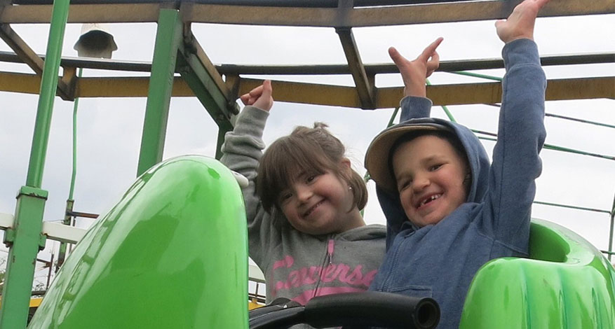 Two children who attend Kids Care playing on jungle gym.