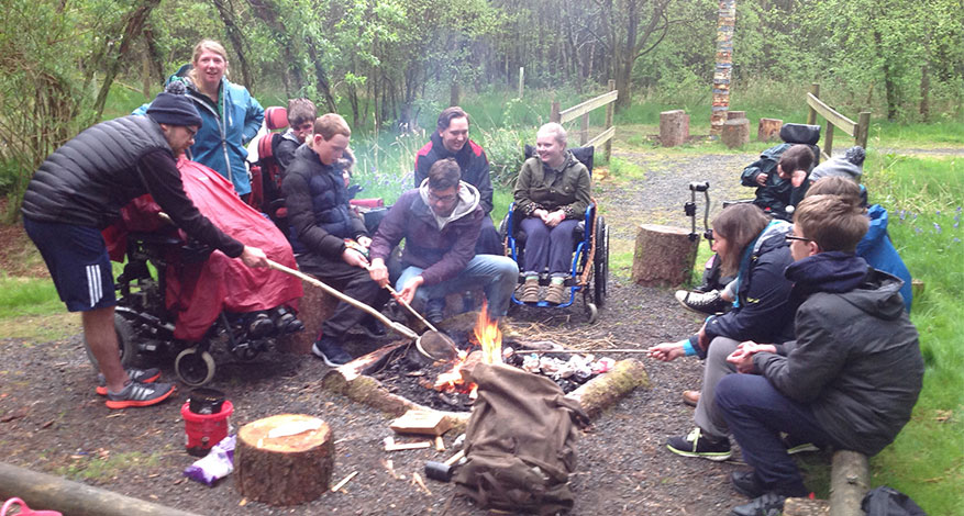 Disabled pupils of Lonsdale School sit round a fire during camping trip.