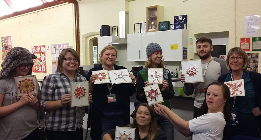 Children show Christmas cards they made with charity Accuro.