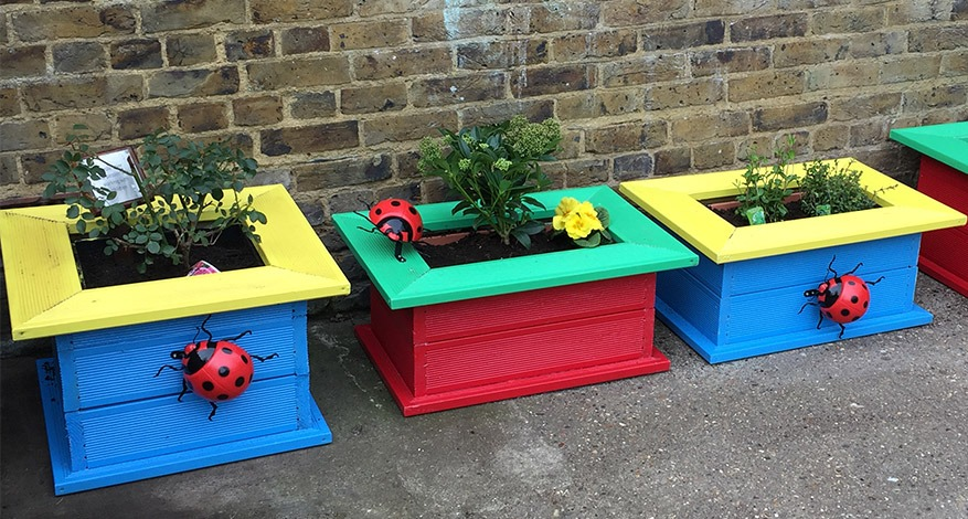 Colourful planters with large ladybird models at Carmel Caterpillars pre-school