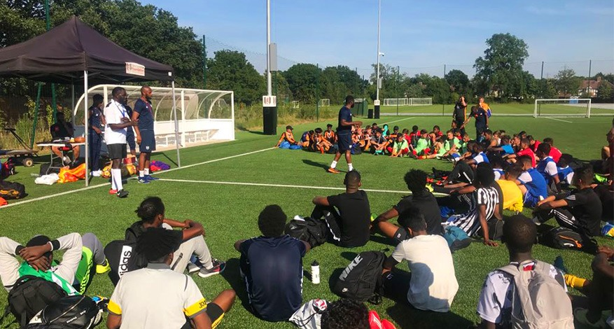 Imber Metz football players sat on a pitch listening to their trainer.