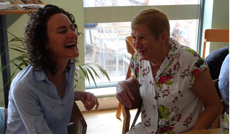 Two ladies at Omega life care laughing together.