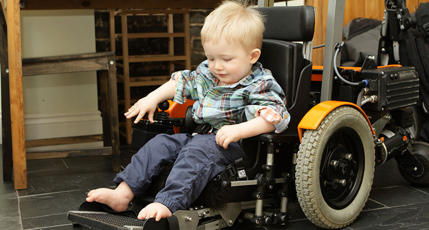 Disabled child in specialist mobility chair