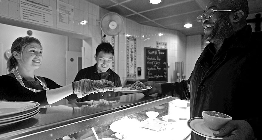 Homeless man being served food in The Passage homeless kitchen.