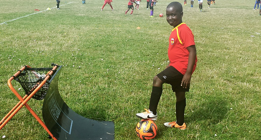 Boy stands on ball next to new sports equipment at Confidence through sport