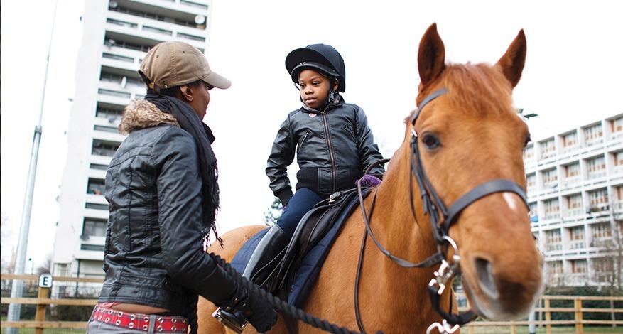 Child learning horse riding at the Ebony Horse Club