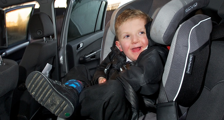 Disabled child smiling in his new specialist car seat