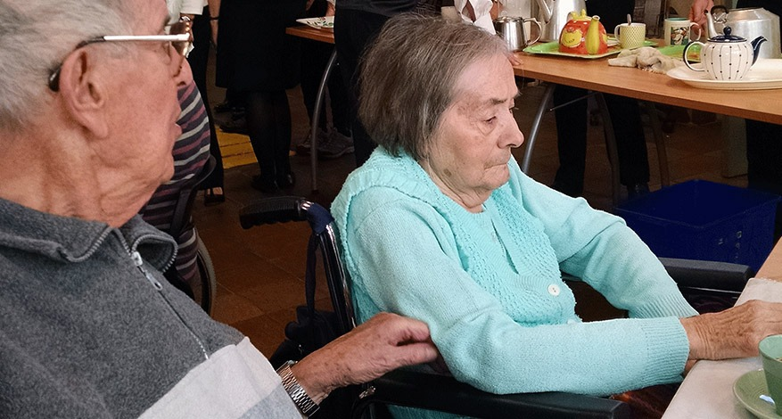 Elderly Woman at daycare centre being supported by unpaid carer