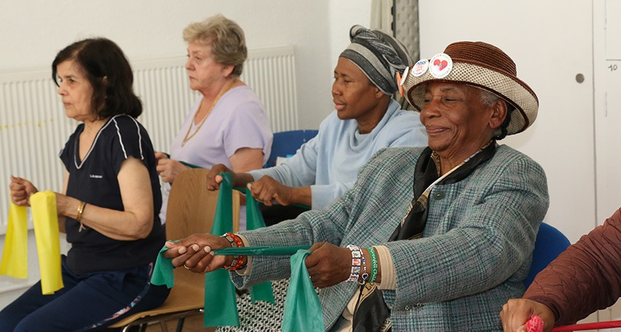 Women in elderly care smiling and holding ribbons at support group