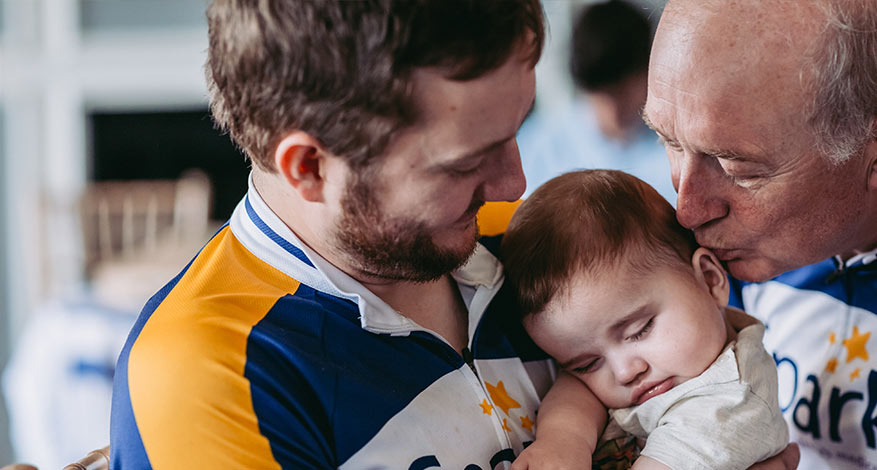 Man holding baby at Sparks Medical Research Charity
