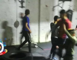 young people in boxing gym with tyre plus 10th anniversary logo