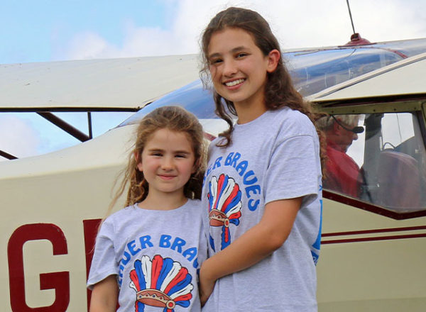 Two young girls stood next to plane at bader braves young aviator day