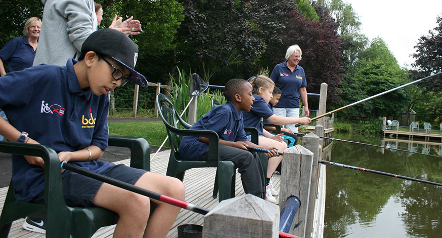 Boy holding a fish with a teacher from the British Disabled Angling Association