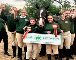 Riders at Scropton Riding for the Disabled with rosettes and a horse