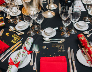dinner table with red napkins, charity ball programme and Christmas Crackers