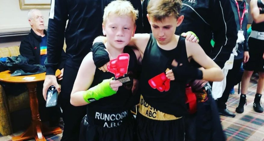 Two young boxers holding their trophies after a fight