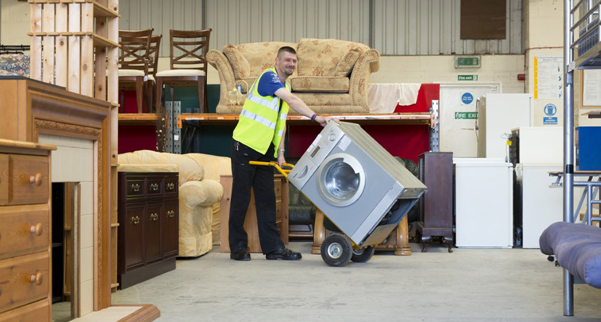 Kennet Furniture, man in high vis jacket in store room of furniture and white goods
